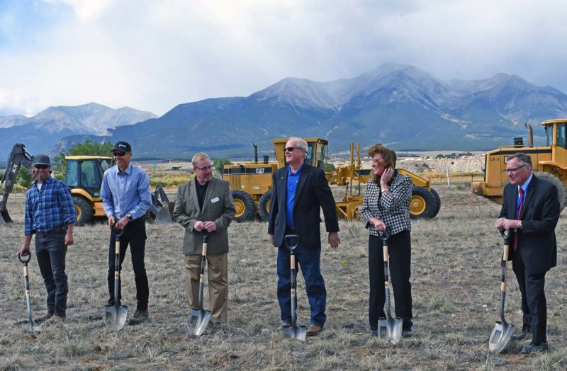 several people standing in a row holding shovels