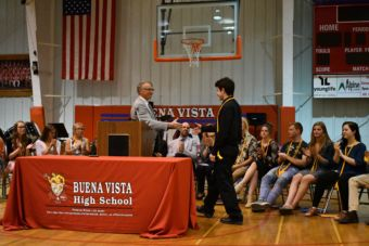 A student shakes hands with a man at a podium at Buena Vista High School