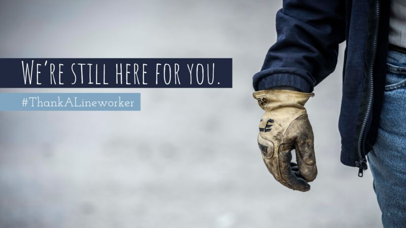 Worker wearing heavy duty work clothing. Text: We're still here for you. #ThankALineworker