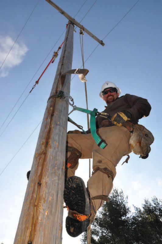 Powerline employee on telephone pole