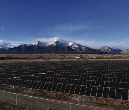 Solar panels in a field with mountains in distance