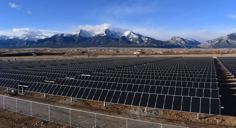 rows of solar panels with mountains in the back