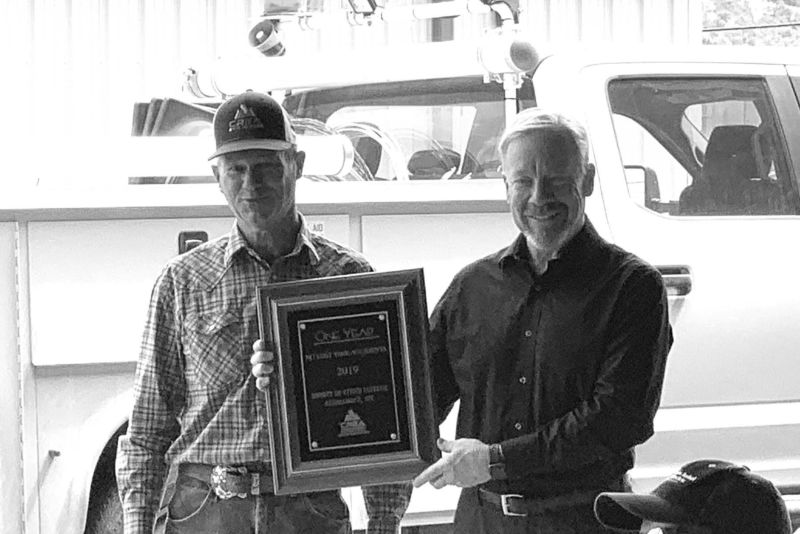 Dan Whitesides, (left) job training and safety instructor for the Colorado Rural Electric Association, presents SDCEA Chief Executive Officer Paul A. Erickson with a plaque commemorating a co-op safety award in August.