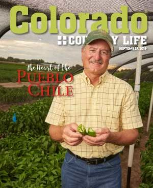 """""""Colorado Country Life September 2019. The Heart of the Pueblo Chili."""" Man standing in field holding chili peppers."""