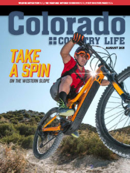 man on mountain bike on August 2021 Colorado Country Life cover
