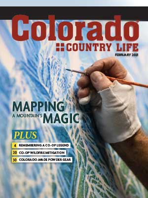 Hand on map on cover of February 2021 Colorado Country Life magazine