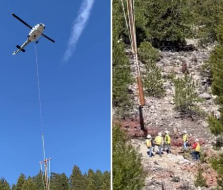 a helicopter carries a power pole down to waiting lineworksers