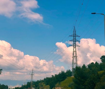 Power poles against a sky with clouds and above a forest