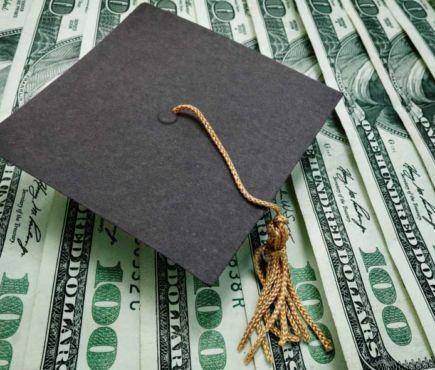 Graduation cap on top of money